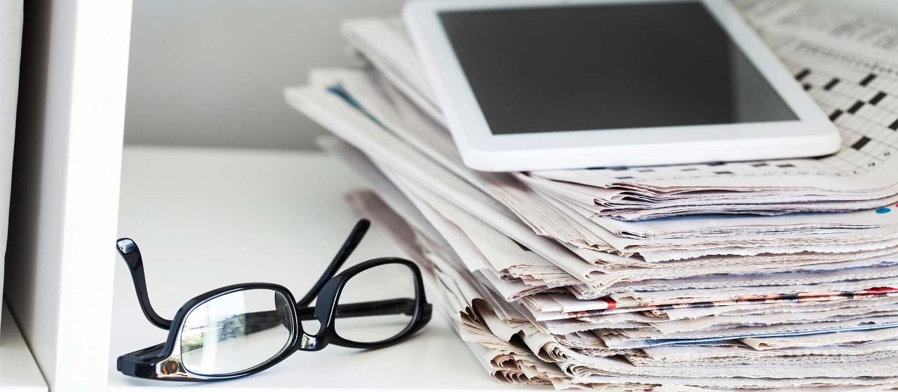 Lesebrille mit Zeitungsstapel